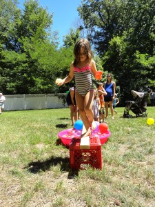 Violet treads our balance beam while carrying two water balloons.