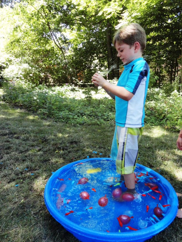 Demetri pops a water balloon with his bare hands. The challenge is to see how many balloons you can burst in 30 seconds.