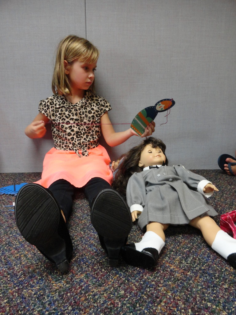 Emma practices sewing on a paper doll that resembles a Matryoshka.