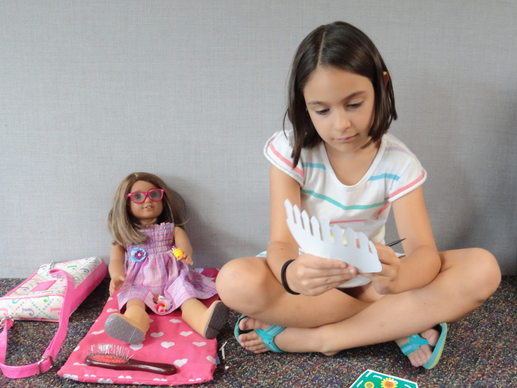 Sabrina (pictured with Rosie) works on her craft during the most recent meeting of our American Girl Book Club.
