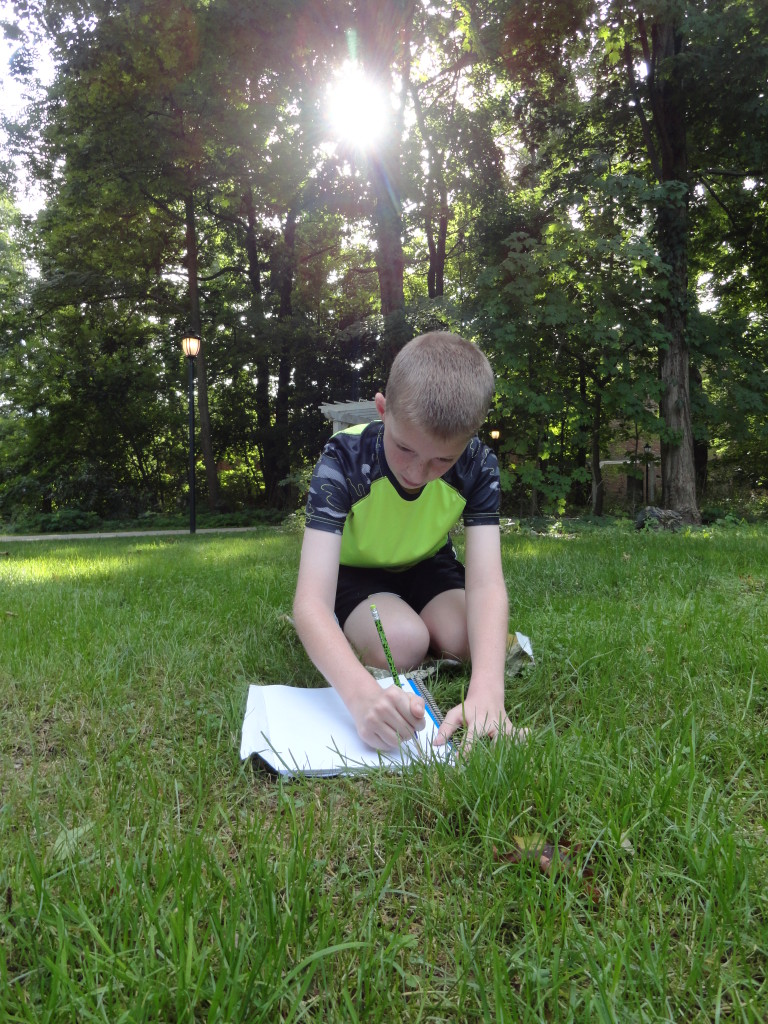 Josh finds a shady spot in our Read House yard to write in his nature journal.