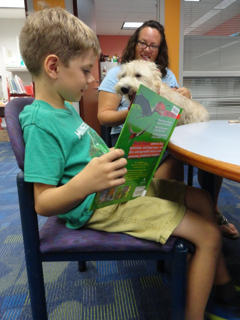 Demetri reads to Hattie about dinosaurs during Paws to Read at Mentor Public Library.