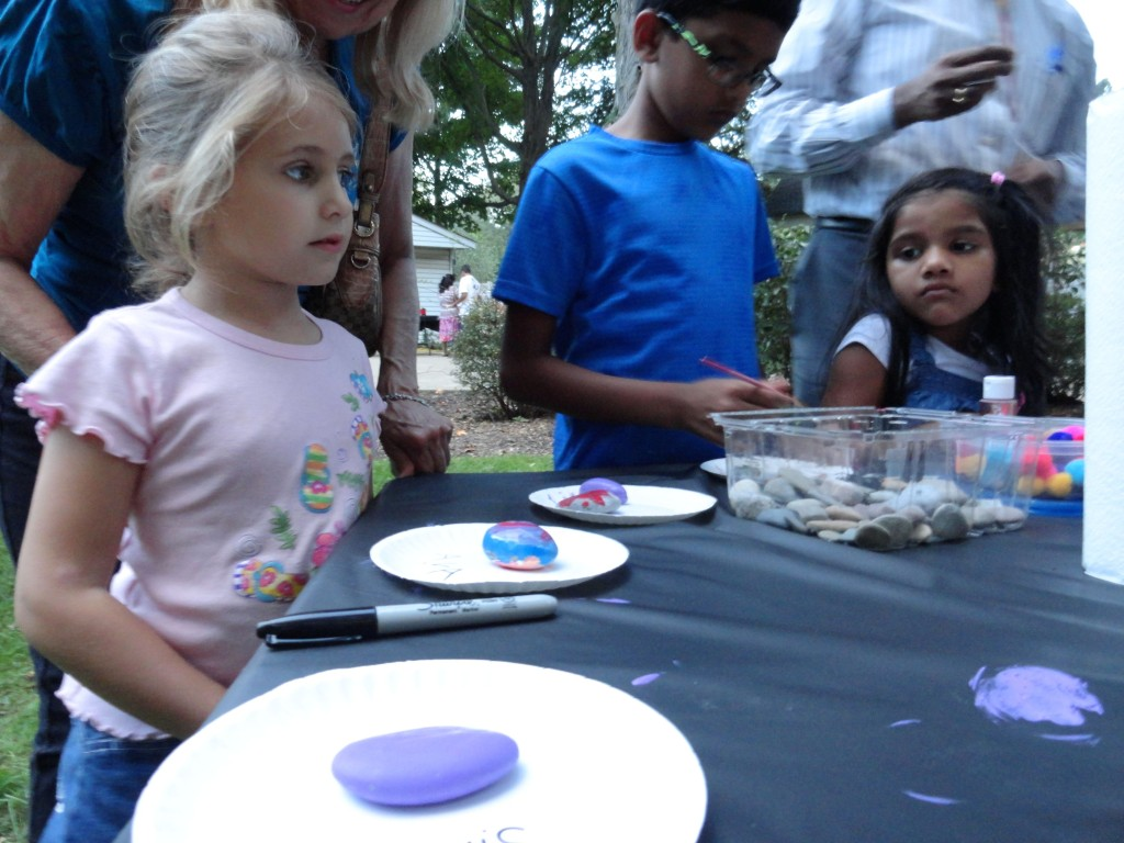 Ava tries to decide what color paint she wants next for her pet rock.
