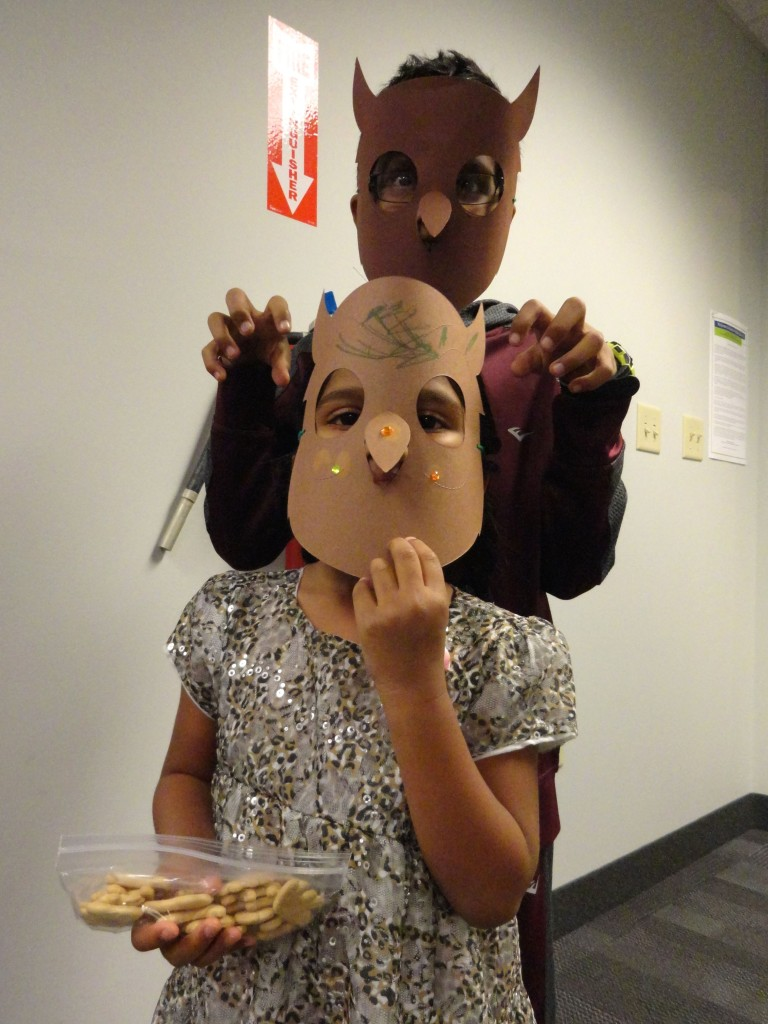 Santosh Akilesh and Diya show off the owl masks that they made at our program.