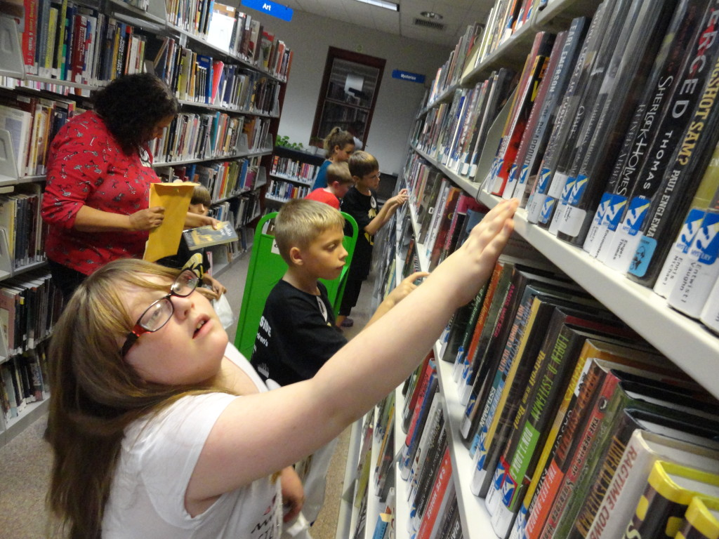 The kids search our shelves for books to complete one of the nine challenges from our Lock-In.