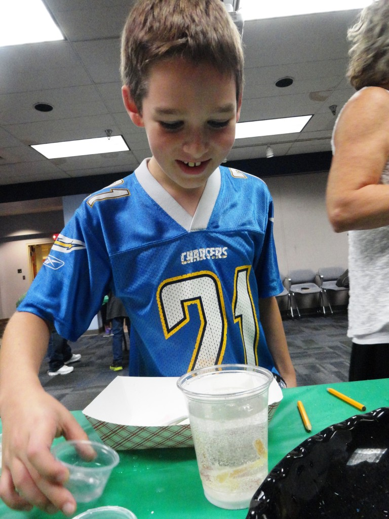 Landon adds a cup of vinegar to his experiment.