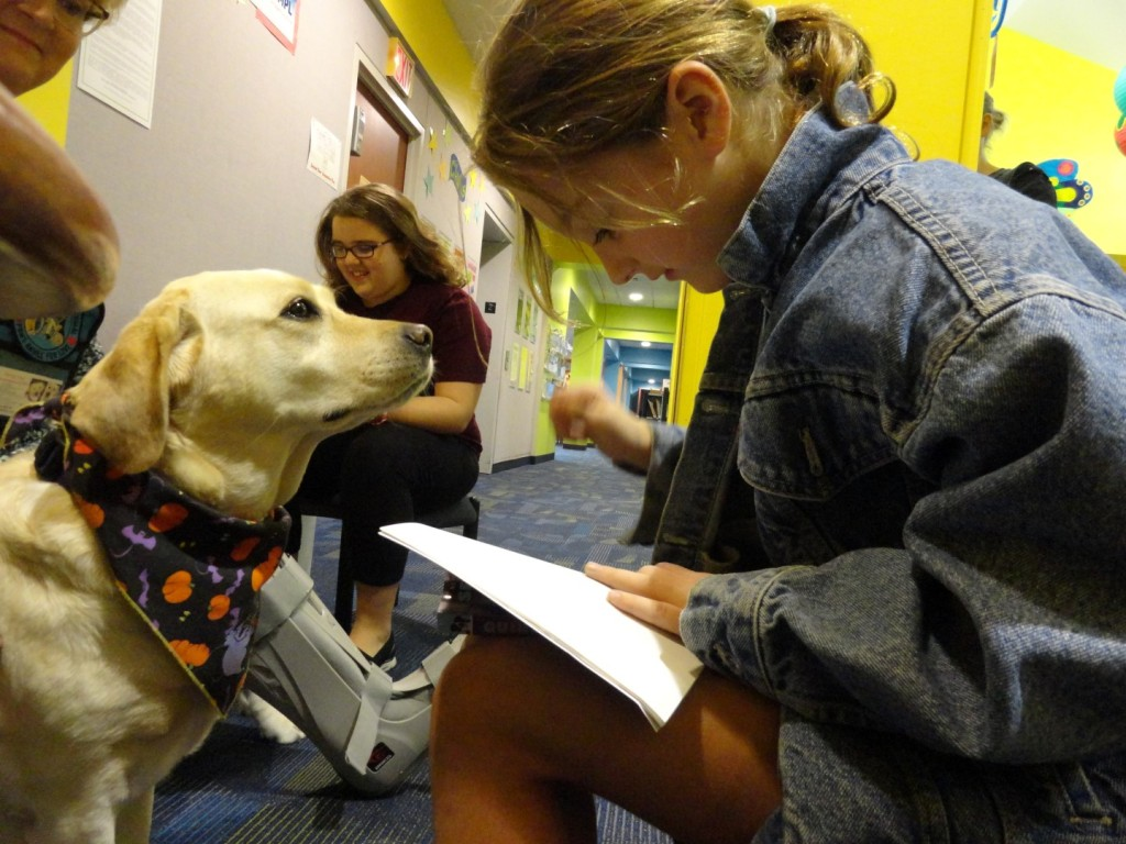 Honey listens attentively to Lily while she reads.