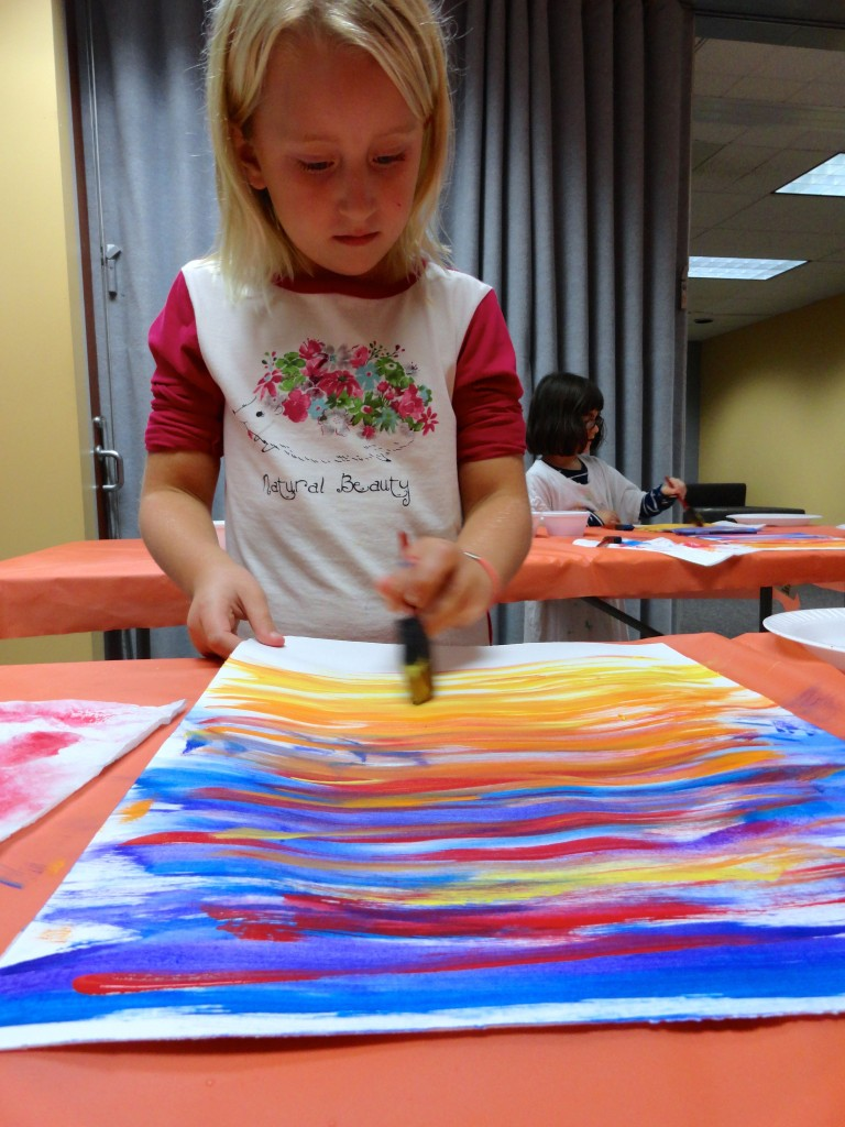 Claire carefully layers her colorful streaks, mixing warm and cold hues.