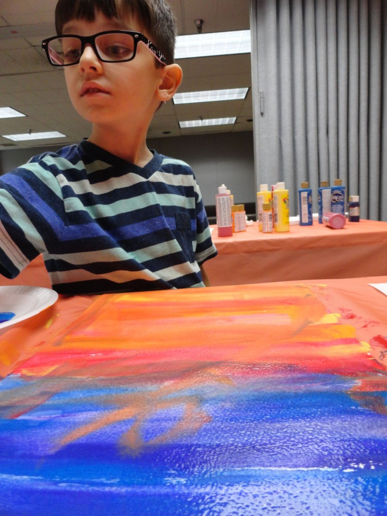 Eli uses water to mix and melt the colors in his sunset together.