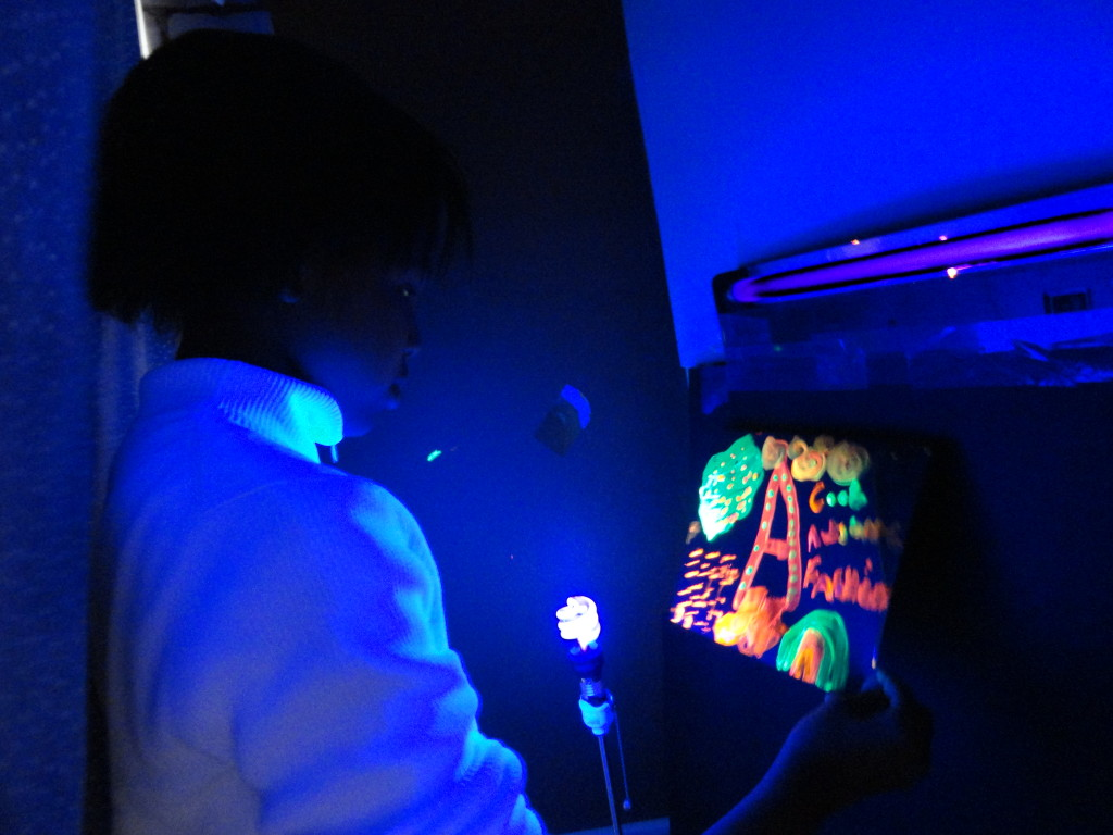 Amerie's paint glows beneath the black light.