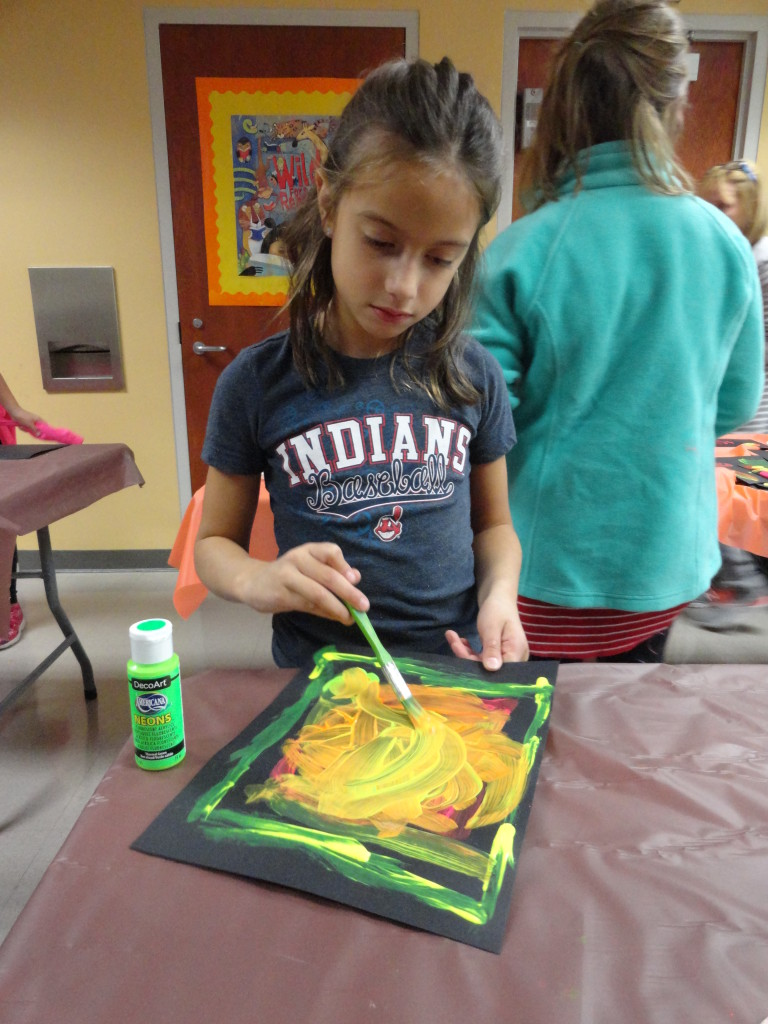 One young artist prepares her work for the glow light.