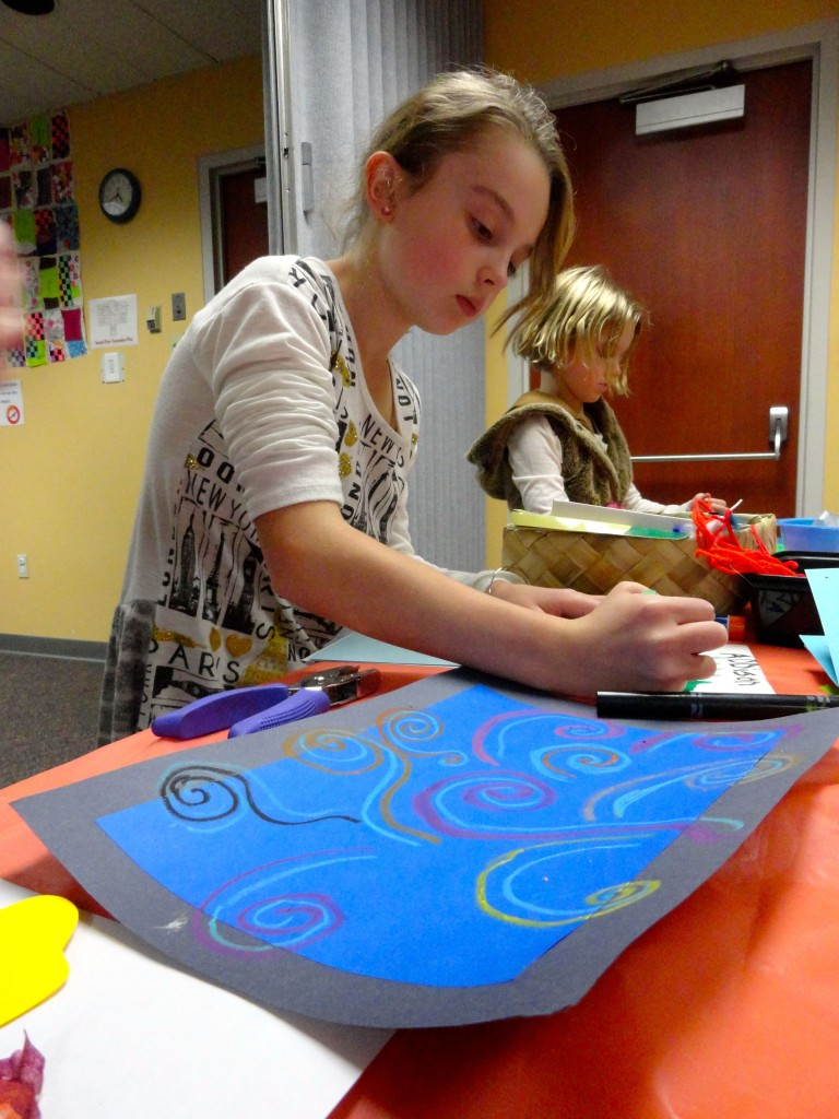 Addison uses pastels to add swirls of wind to her frame.