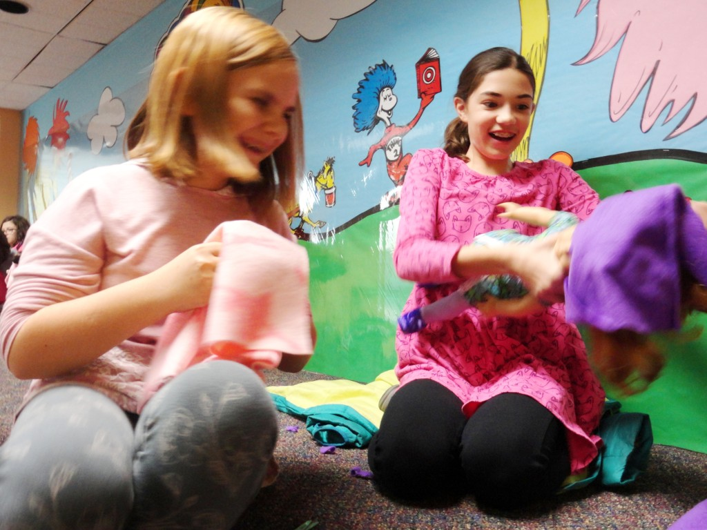 Isabella laughs while Abby tries to squeeze her doll into a purple poncho during our American Girl Book Club meeting.
