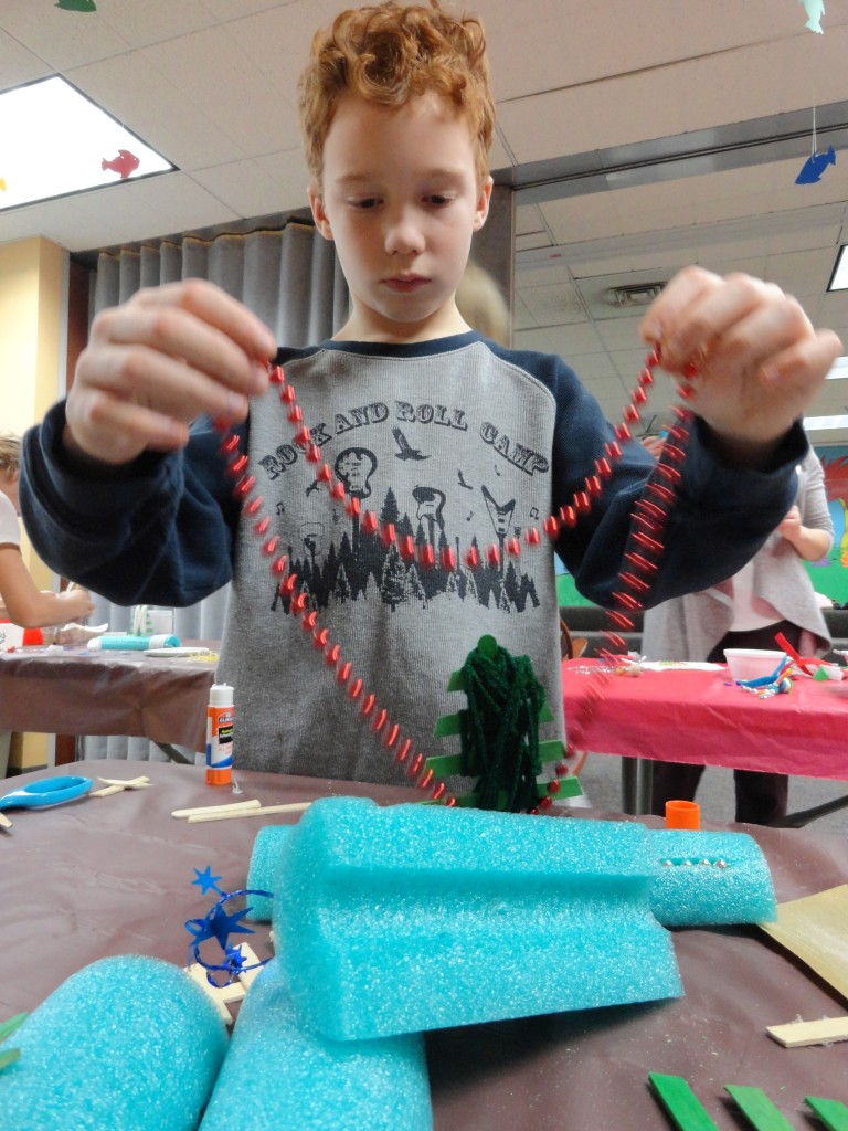 Andrew tries to decide how he's going to turn a red beaded necklace into ornaments for his tree.