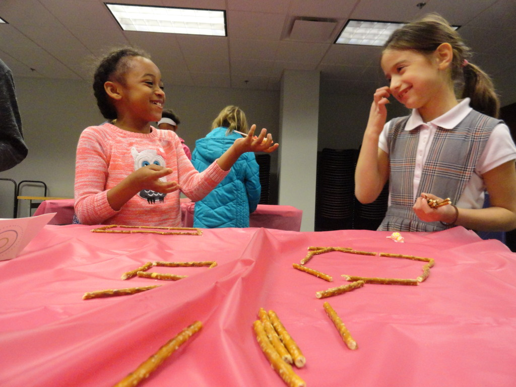 Aniyah and Sarah turn their pretzel shapes into a snack during the STEAM program at Mentor Public Library.