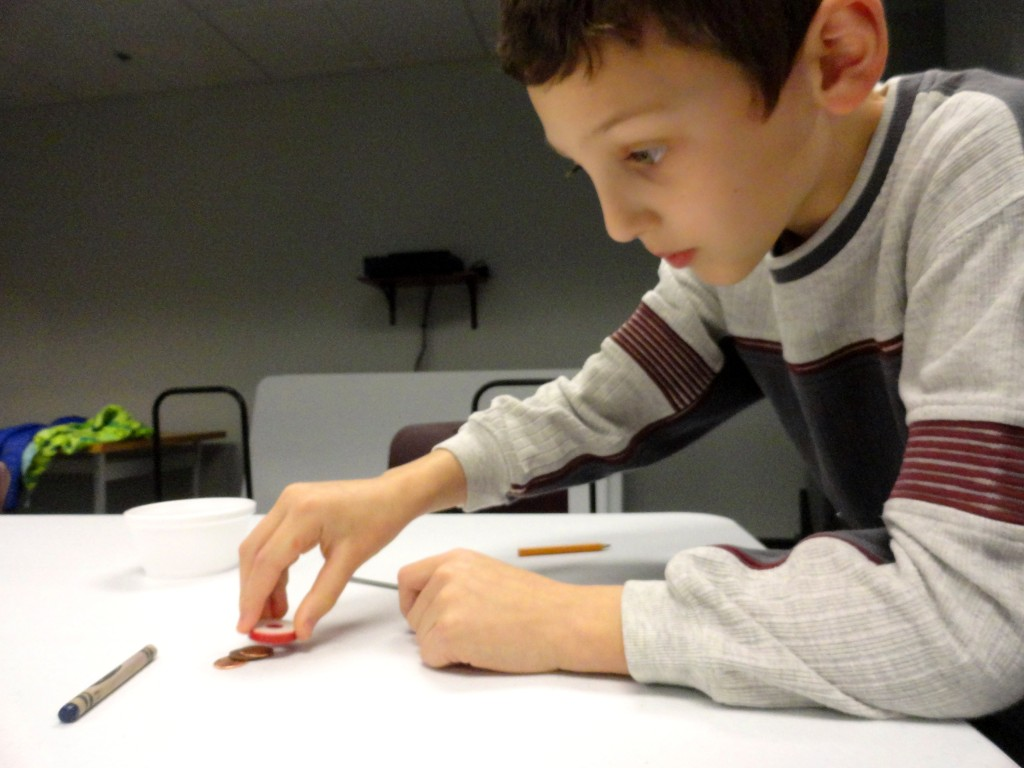 Darin tests different substances, from pennies to pencils, to see if his magnet moves them.