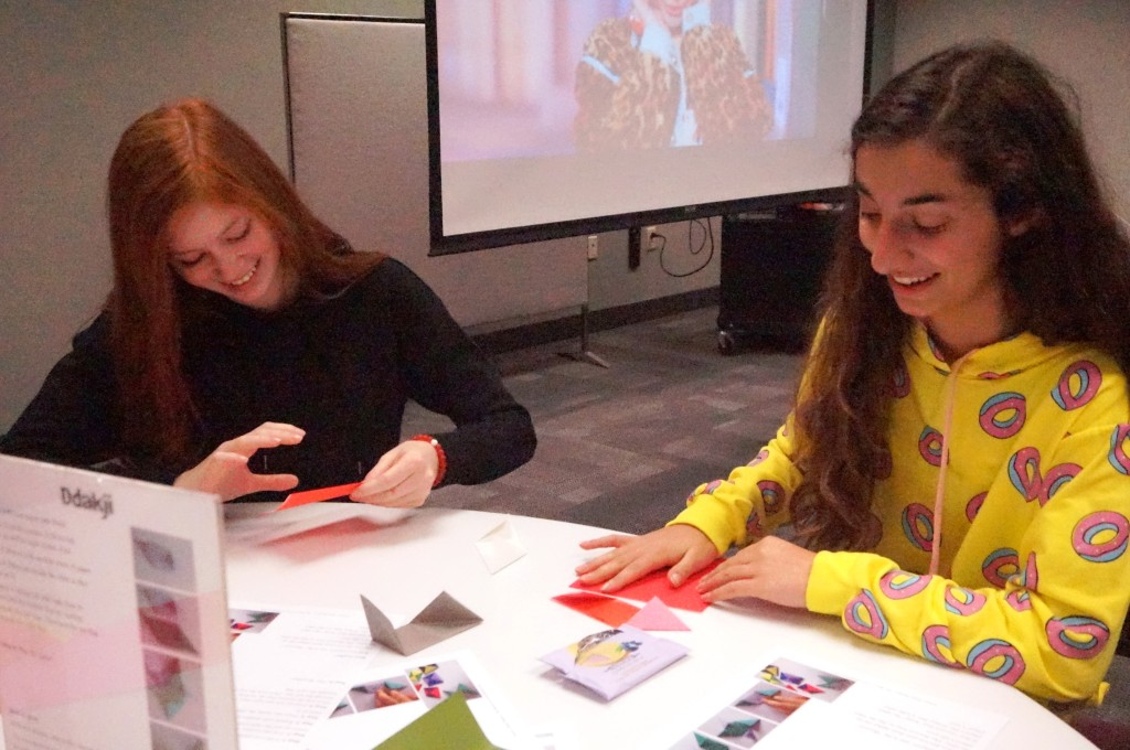 Teens learn how to play ddakji, a game that's similar to pogs and uses origami pieces.