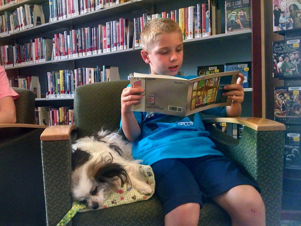 AJ and Caesar share a book during Paws to Read at our Lake Branch.