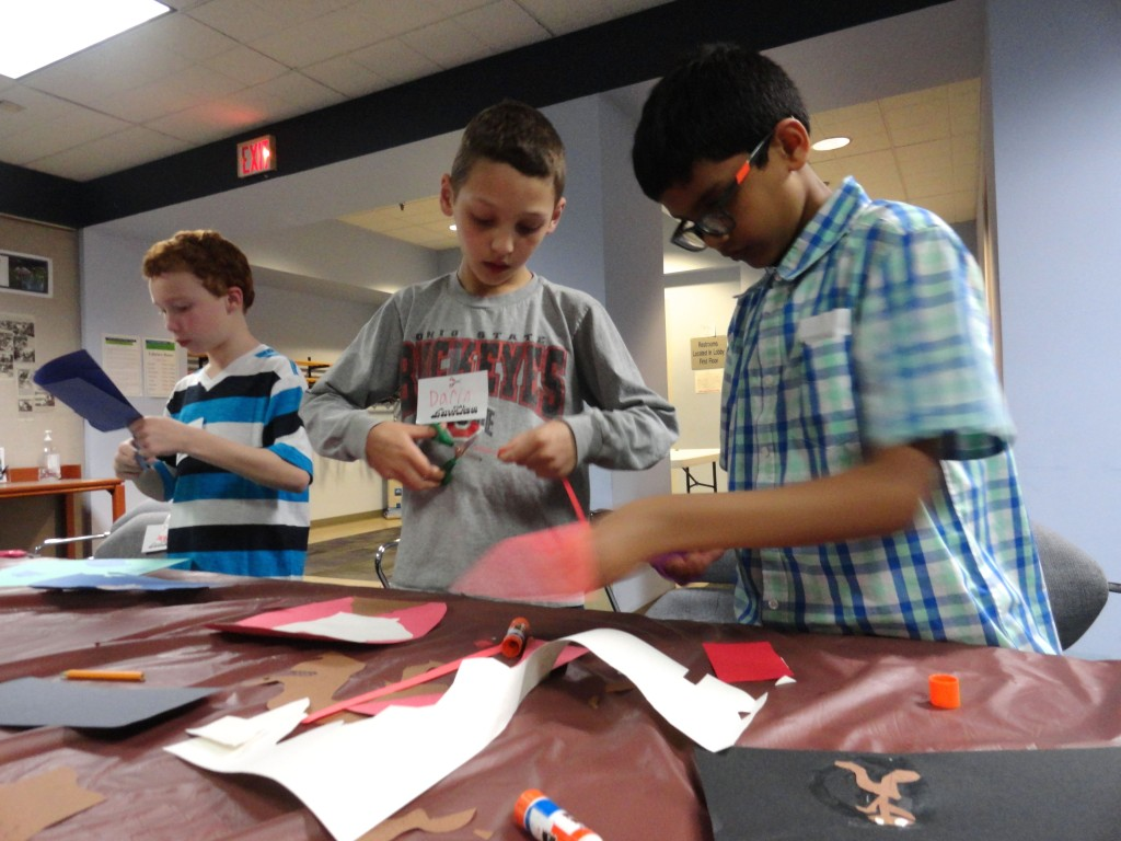 Andrew, Darin, and Santosh Akilesh cut shapes from the construction paper for their collages.
