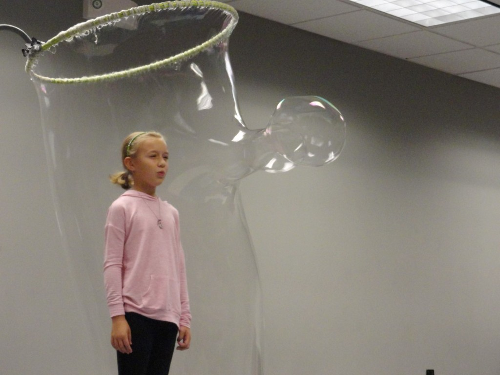 Eva blows a bubble of her own from inside the bubble.