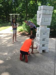 Kids playing Jenga with oversized blocks.