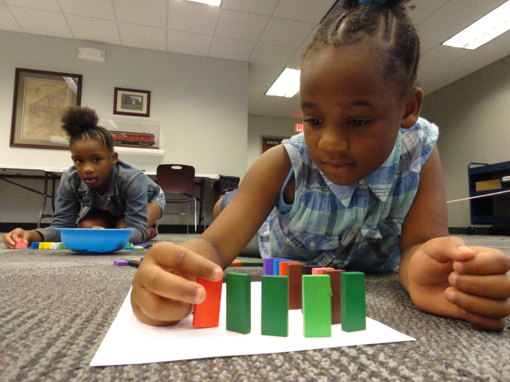 A'zariah adds a curve to her domino run.