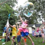 Children play with enormous bubbles made by Ed Molesch during the Summer Reading Finale Party at Mentor Public Library's Read House.