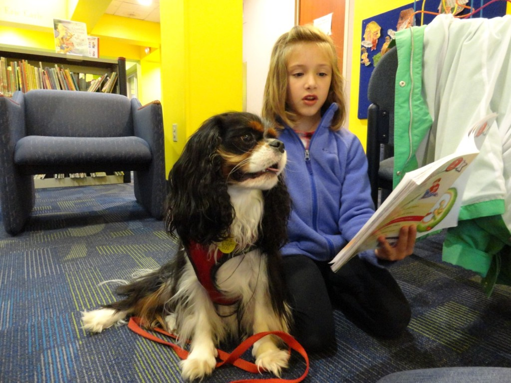 Wesley snuggles in as Claire reads to her during Paws to Read at Mentor Public Library.