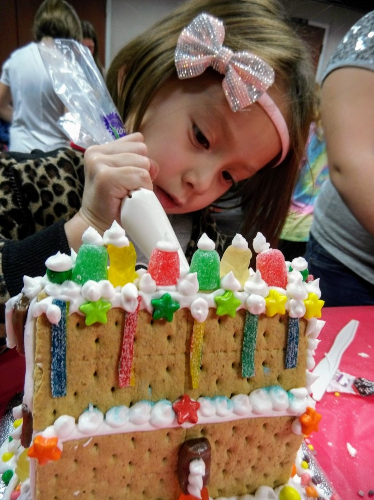 Amber Maltba adds the finishing touches to her graham-cracker house during a Holiday House Party