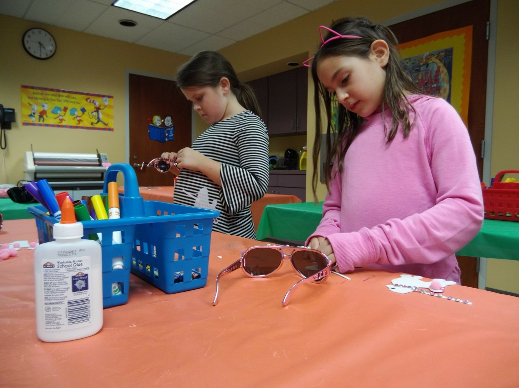 Our American Girl Book Club bedazzles sunglasses during their most recent meeting.