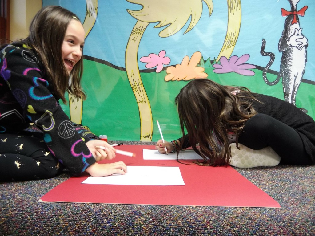 Sabrina and Taryn laugh as they sketch their pets.