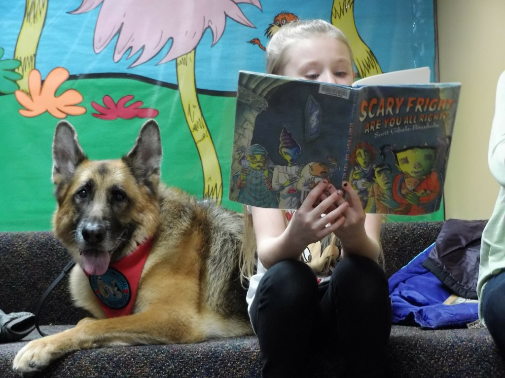 Autumn shares a book with Diva during Paws to Read at Mentor Public Library.