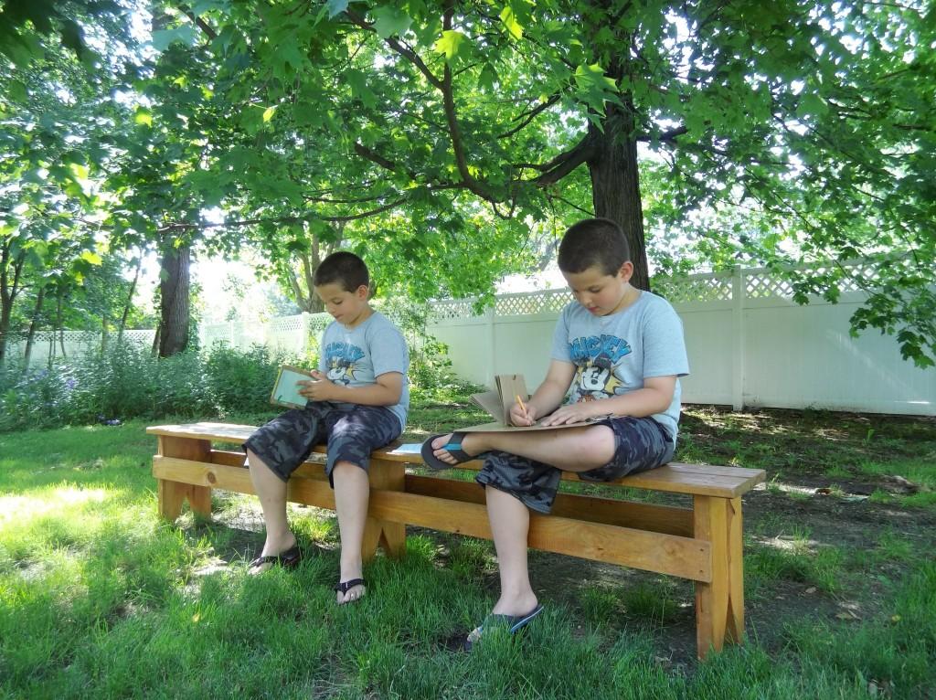 John and Julian jot beneath a shady tree.