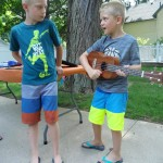 Liam gives one of our new ukuleles a strum. (Can't say for sure if his brother appreciates the concert.)