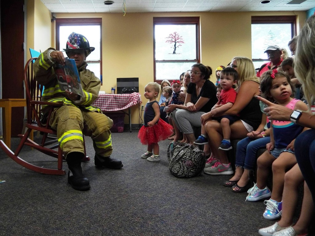 Mentor Firefighter Jerry Craddock reads to the children about what it's like work at the fire department.