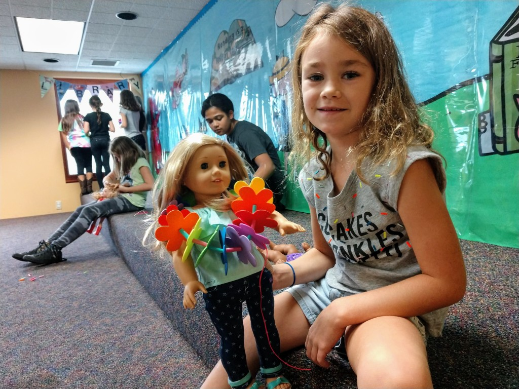 Sadie shares her lei with her doll during our American Girl Book Club meeting.
