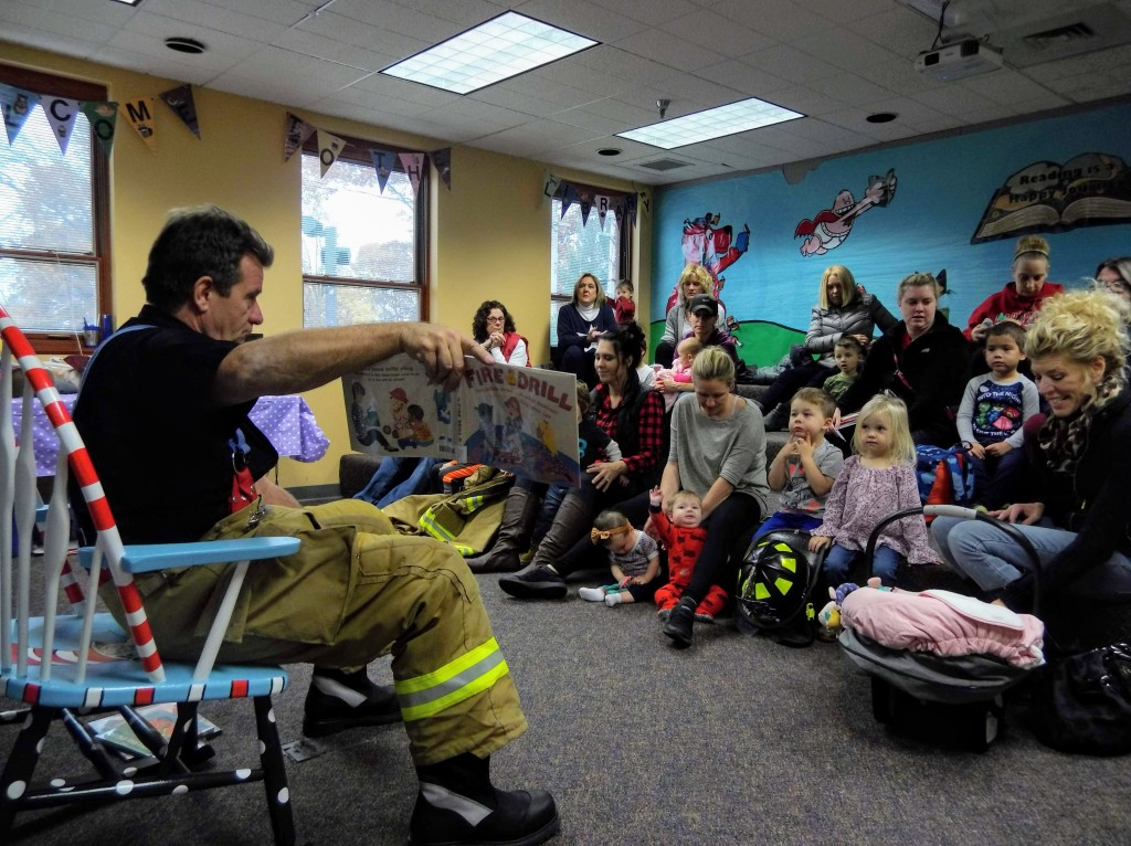 Firefighter Jerry reads to the kids about fire safety.