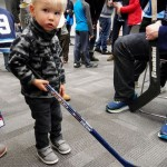 Wesley handles the goalie stick after story time.