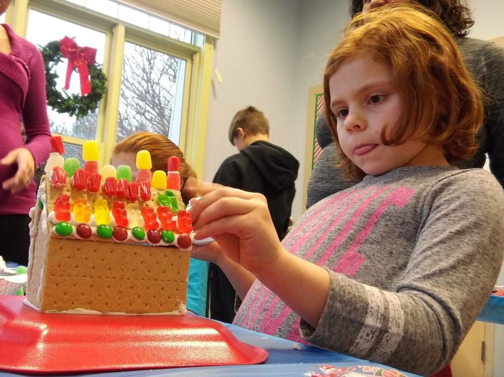 Emily carefully festoons her graham-cracker house with frosting and gumdrops.