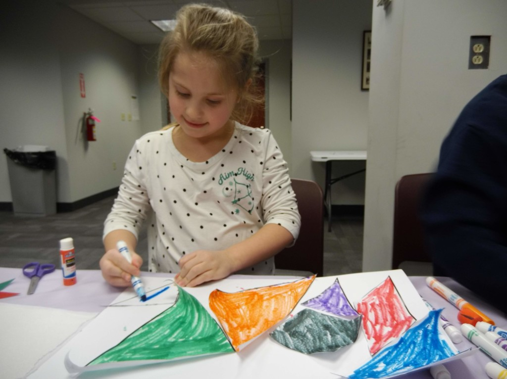Kids assemble their shapes into different pictures during our tangram program.
