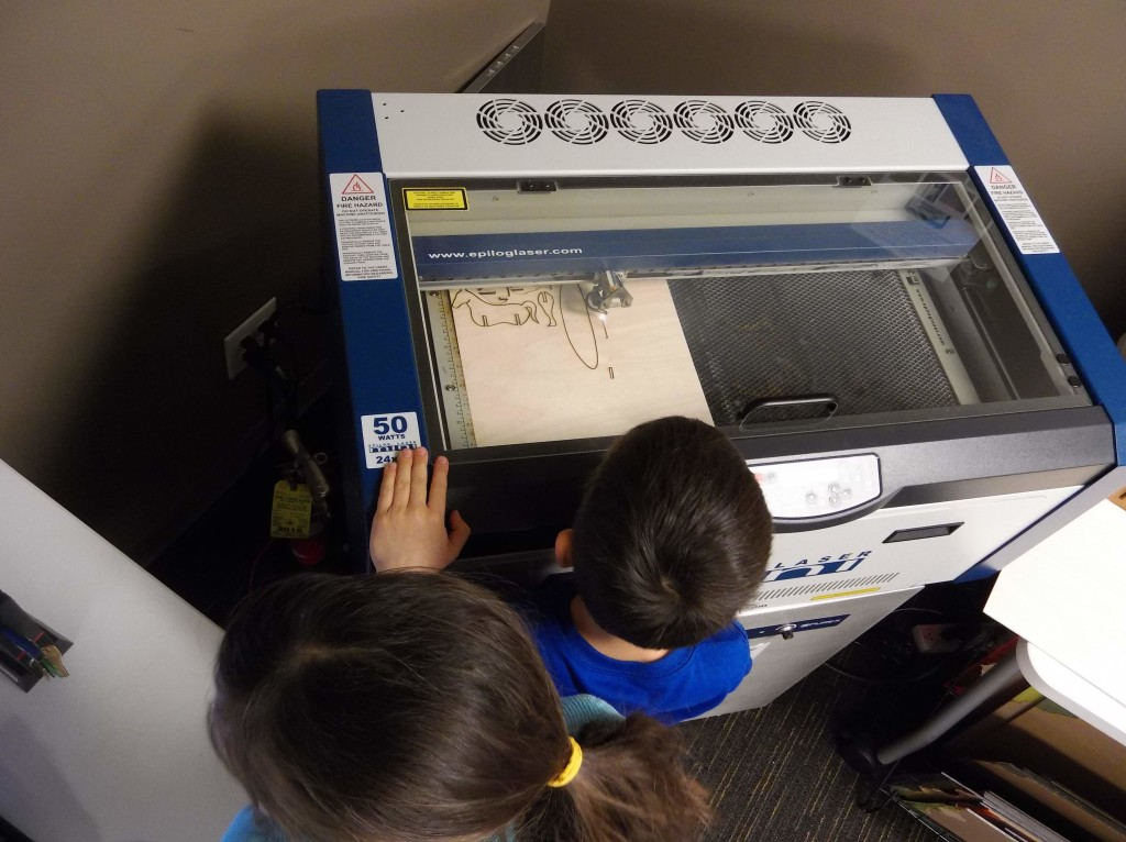 Olivia and Kyle watch as the laser engraver carves the pieces of a wooden toy for them to assemble.