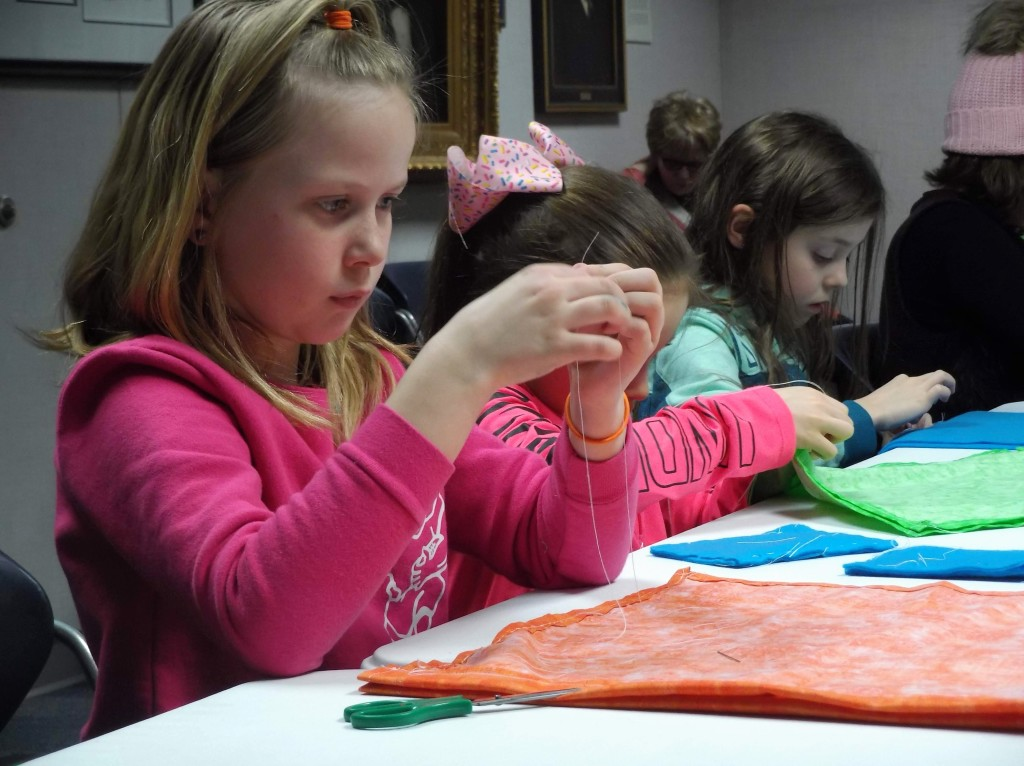 Kids practice sewing at the library by making drawstring backpacks or Fortnite drop pillows.
