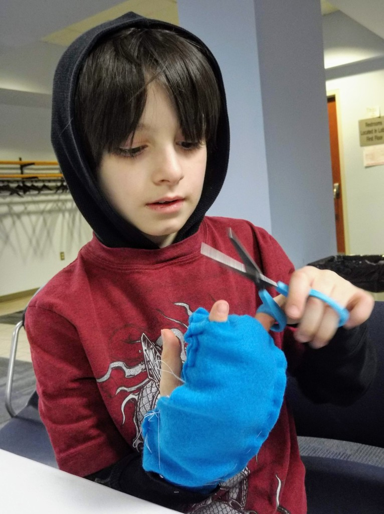 Eli makes himself fingerless gloves.