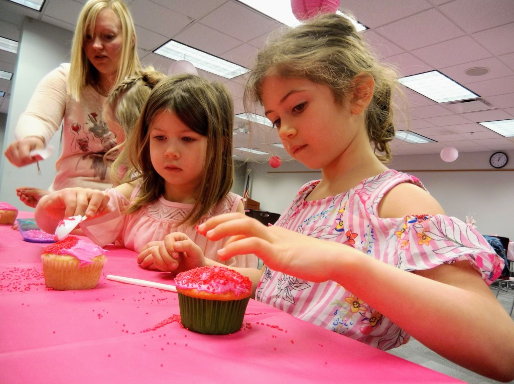 Quinn and Maeve frost and decorate their cupcakes.