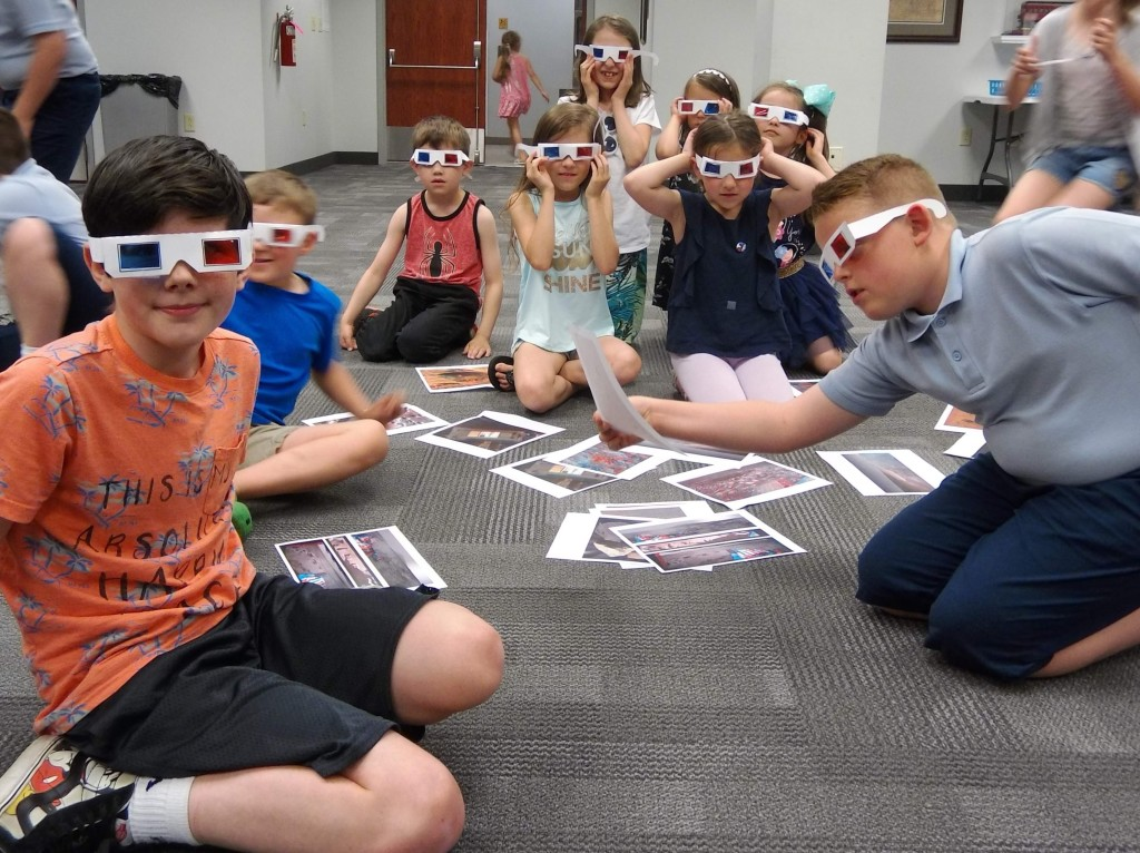 Kids use their 3D glasses to look at photos from the Mars Rover.