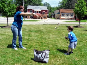 Woman playing with a little boy throwing a ring with sticks