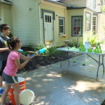 Kids use water guns to see who can knock down cup towers the fastest.