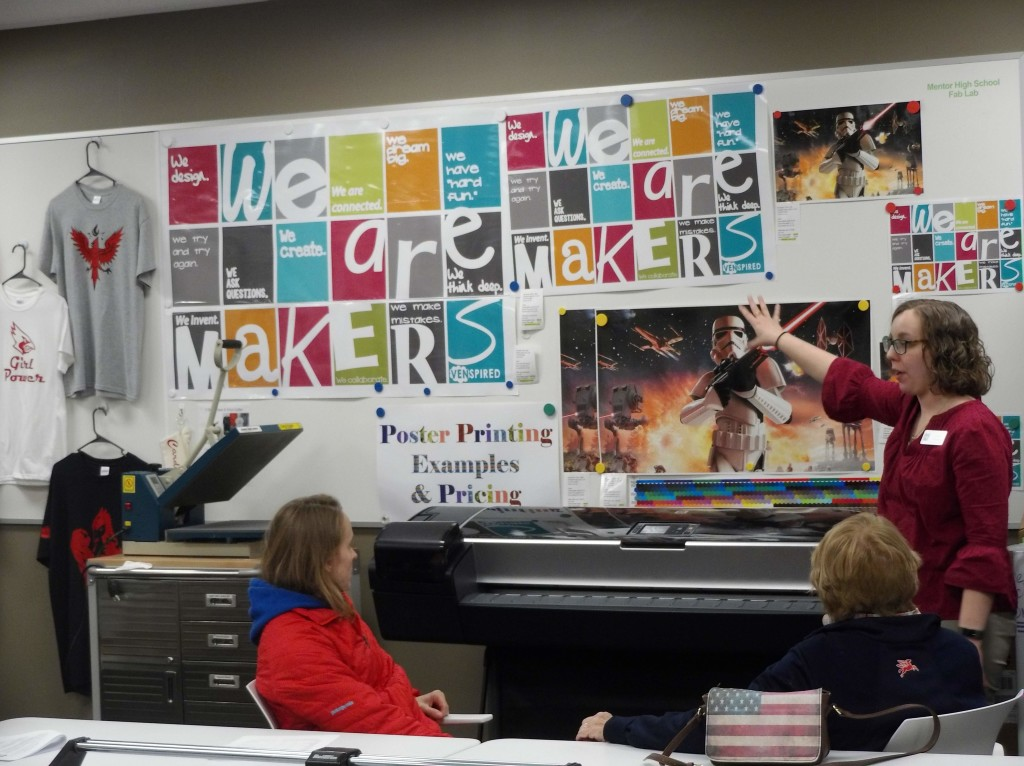 Patrons learn about the large-format printer at The HUB during a makerspace tour.