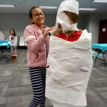 Sarah wraps up Maddie during a mummy race.