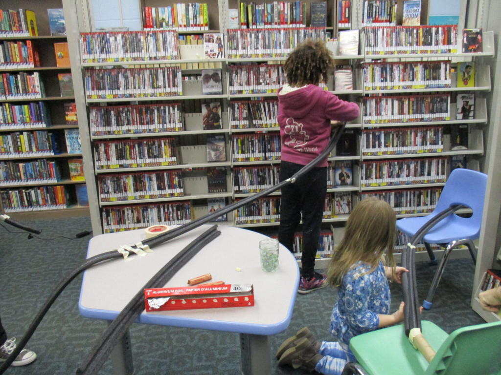 Sissy and Elena build a roller coaster through the shelves of our Headlands Branch.